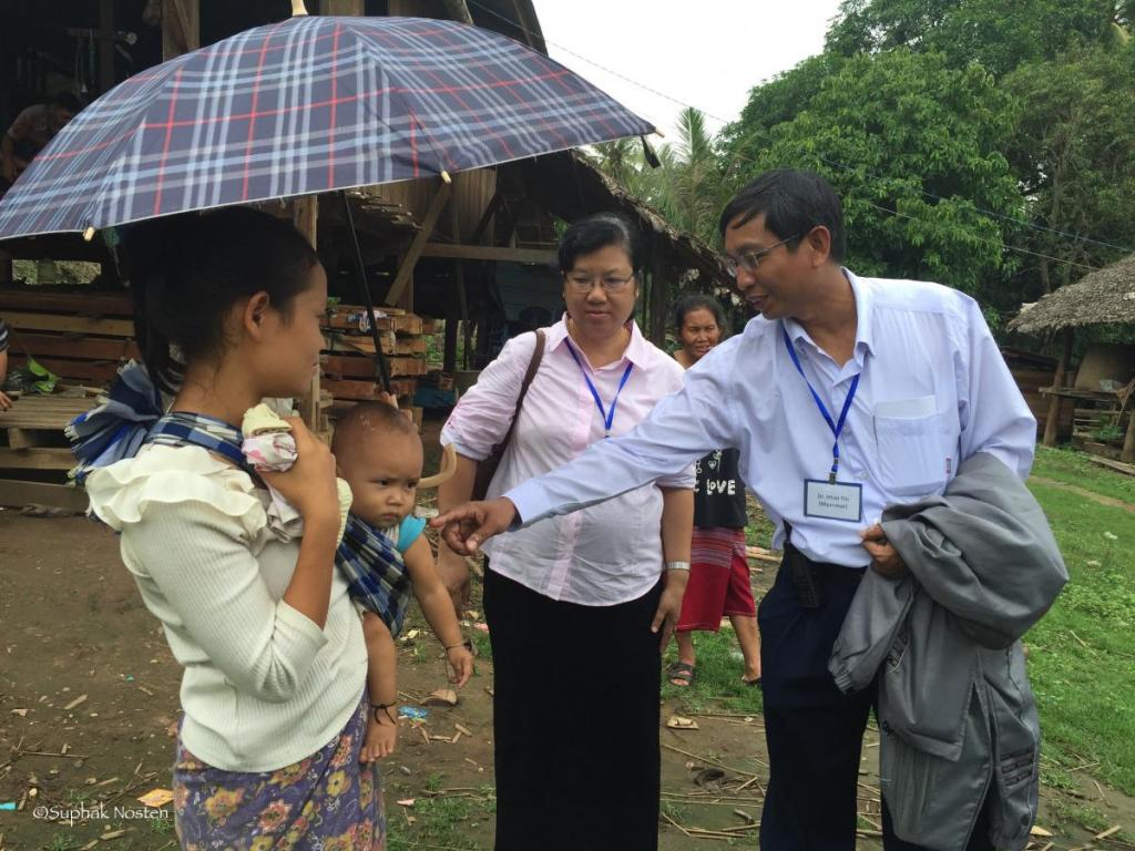 Drs. ThandaLwin and Tun Tin interact with villager
