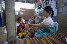 Candy Beau (right), a medic at the Mae Pa clinic, inspects a sick Myanmar child. Candy Beau herself recently contracted Chikungunya and dengue and is dealing with prolonged symptoms. (Luke Duggleby | Frontier)